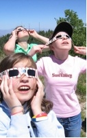 Three young Astronomy Camp students watch a solar eclipse from the 9,157-foot summit of Mt. Lemmon near Tucson.